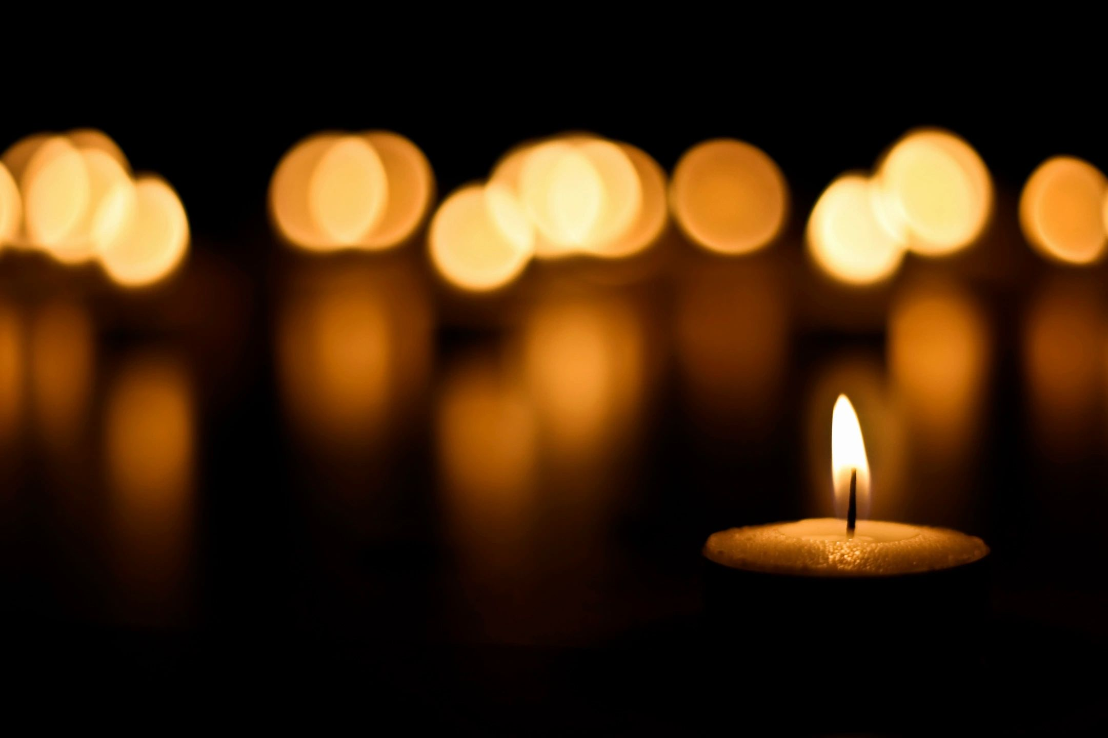 out of focus candles over a dark background