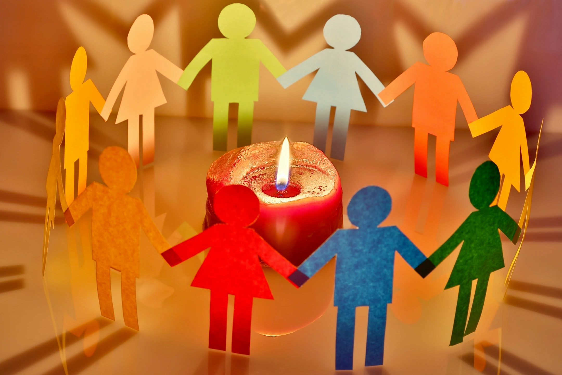 Mulitcolor Paperdolls holding hands around a lighted candle